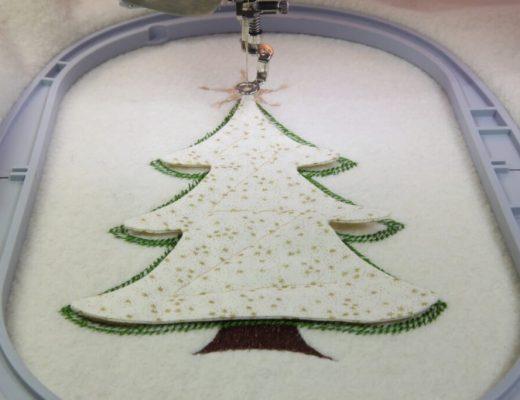 Mit der nächsten Farbe wird der Baum fixiert. Danach muss der lange Heftstich getrennt werden.